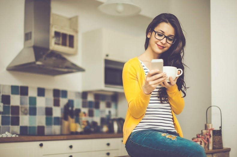 women sitting in the kitchen with phone and mug
